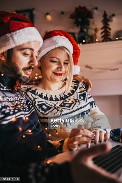 Happy couple looking winter vaction destinations on their laptop, Christmas time