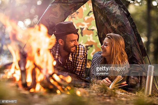 Happy couple lying in tent by campfire and communicating.