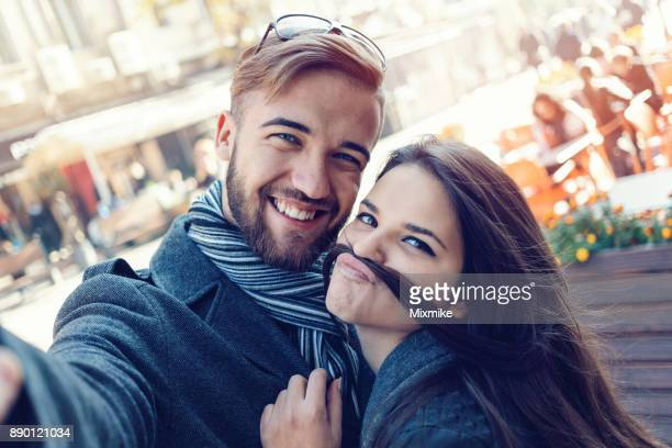 Happy couple making selfies on the street