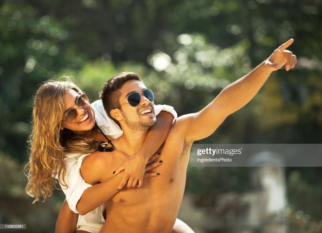 Happy couple, man piggyback a beautiful woman on the beach : Stock Photo