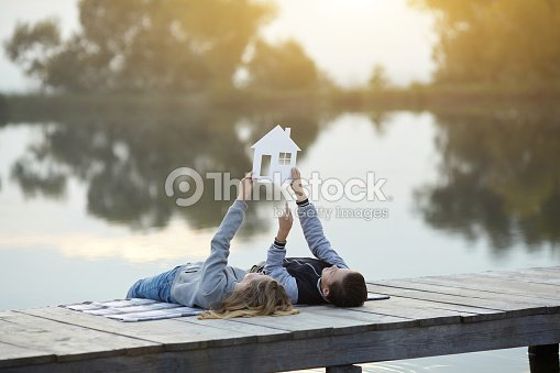 Happy couple of kids dream of a home : Stock Photo