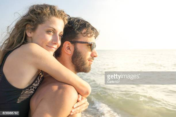 Happy couple of lovers looking the horizon on a Tuscan beach at sunset