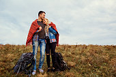 A happy couple of tourists are warming themselves under a plaid in nature.