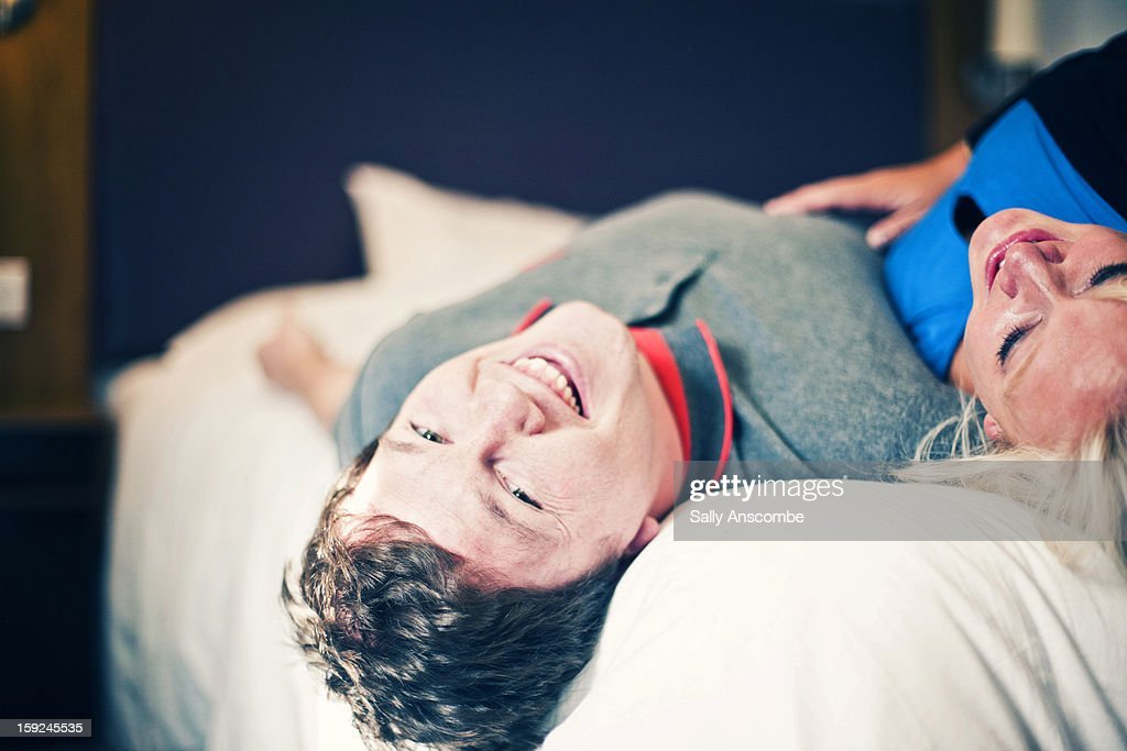 Happy couple on a bed together : Stock Photo