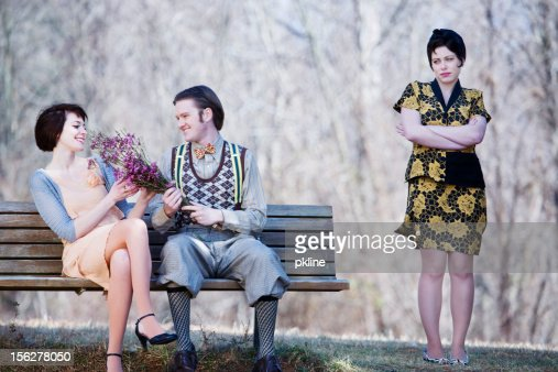 Happy couple on a bench while jealous lady watches
