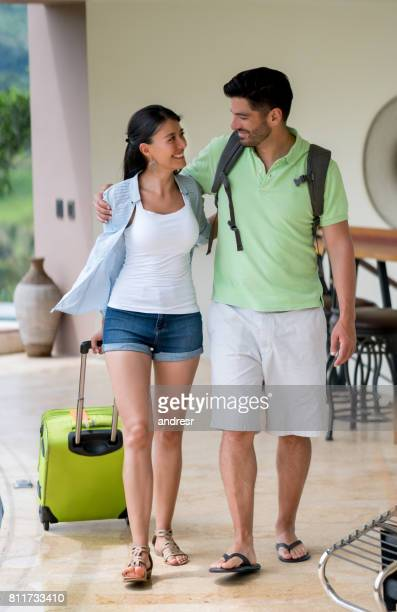 Happy couple on a romantic getaway arriving at their hotel