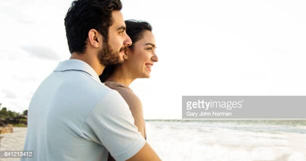 Happy couple on beach looking out to sea.
