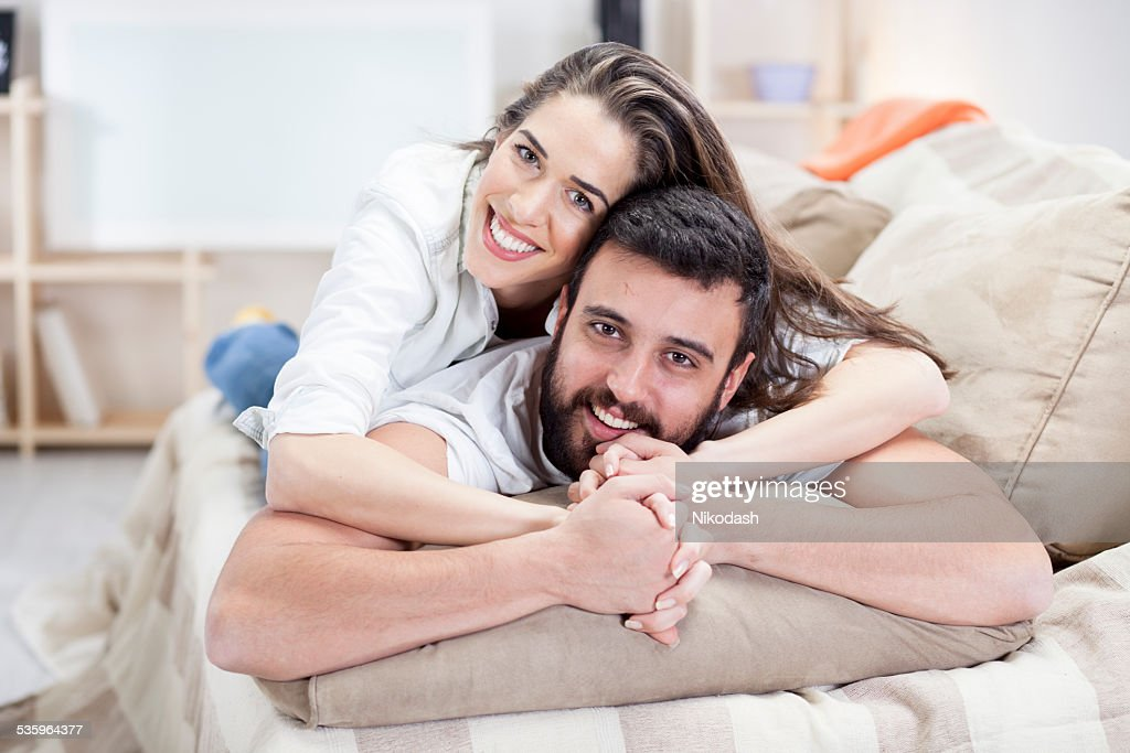 happy couple on bed sofa in living room : Stock Photo