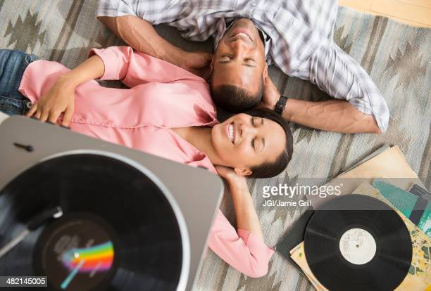 Happy couple on rug listening to record player