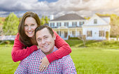 Happy Affectionate Couple Outdoors In Front of Beautiful House.
