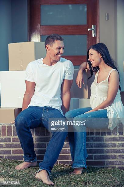 Happy couple outside a house with moving boxes.