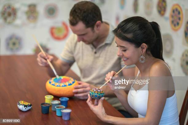 Happy couple painting mandalas on rock stones