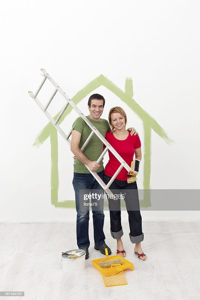 Pareja feliz pintura de su hogar : Foto de stock