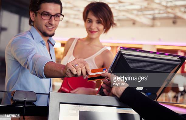 Happy couple paying movie tickets with credit card