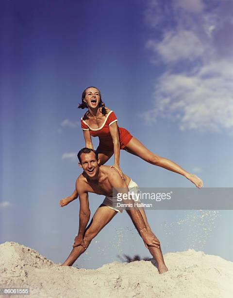 Happy Couple Playing Leapfrog at Beach