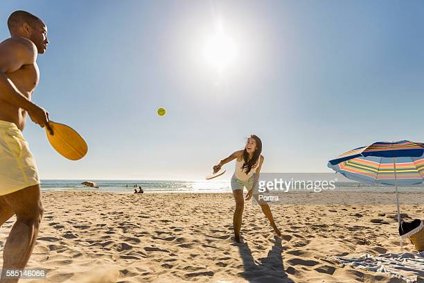Happy couple playing tennis at beach on sunny day