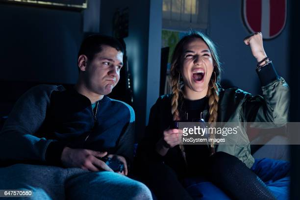 Happy couple playing video games and having fun together.
