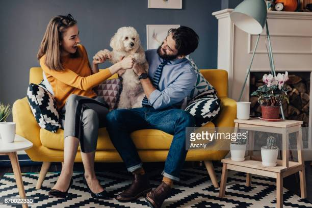 Happy couple playing with a dog