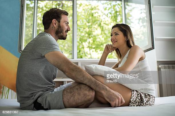 Happy couple relaxing in bedroom and talking to each other.