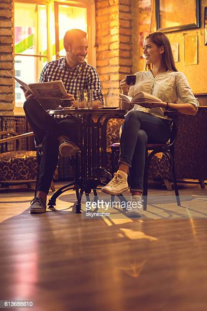 Happy couple relaxing in cafe and talking to each other.