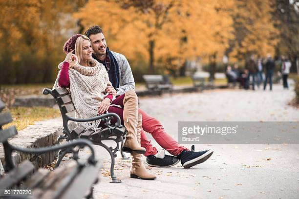 Happy couple relaxing on a bench in the park.