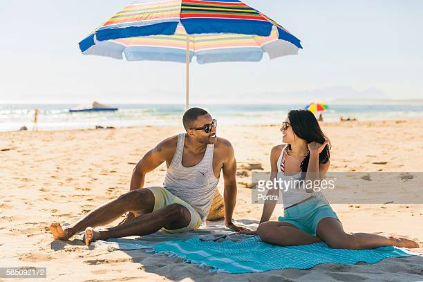 Happy couple relaxing on shore at beach