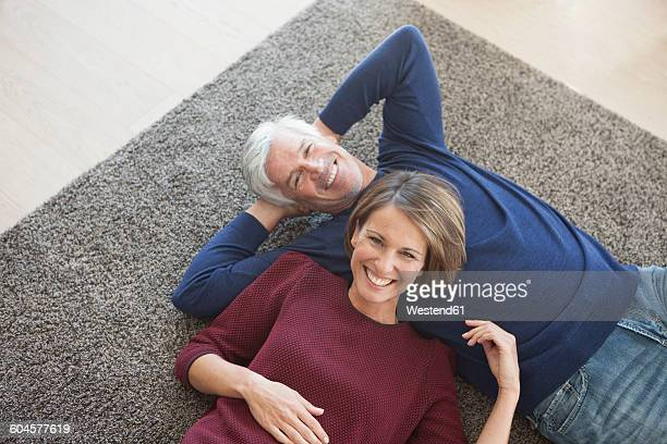 Happy couple relaxing together on the carpet