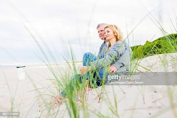 Happy couple resting on sandy beach