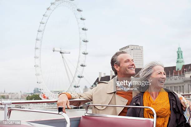 Happy couple riding double decker bus in London