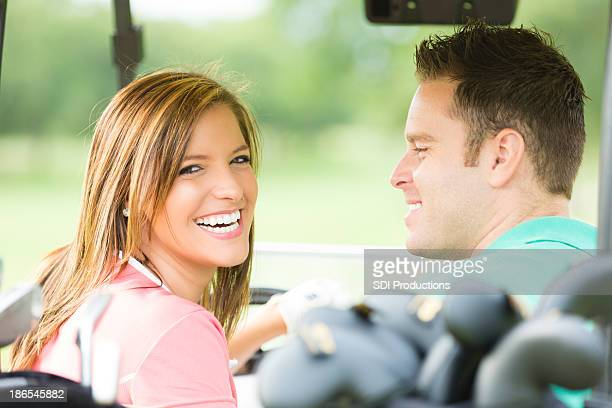 Happy couple riding in golf cart during game