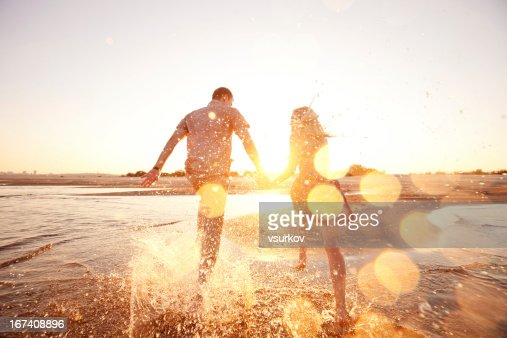 A happy couple runs through waves on sunlit beach : Stock Photo