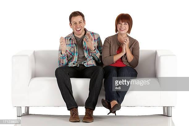 Glückliches Paar auf einer couch zum Sitzen und Klatschen