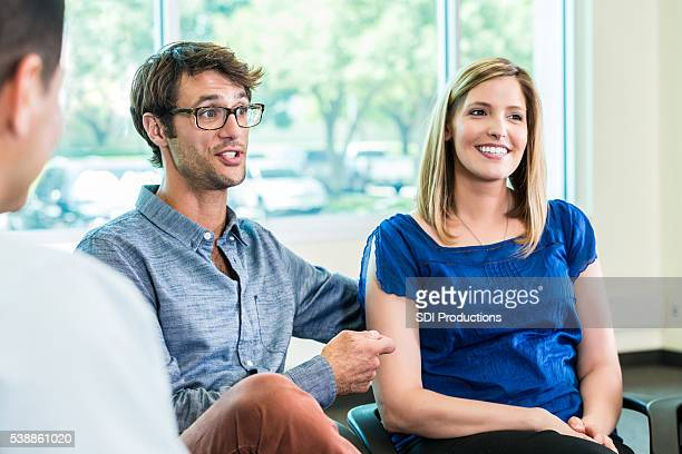 Happy couple sitting at meeting together