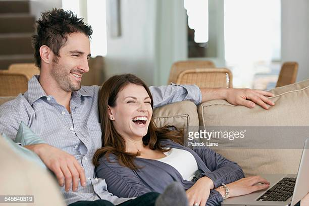 Happy couple sitting in sofa and using laptop
