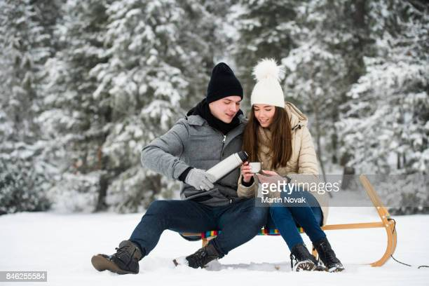 Happy couple sitting on sled and drinking tea