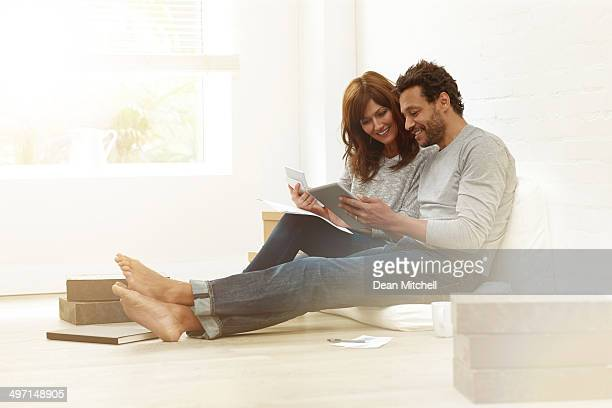 Happy couple sitting together calculating their expenses