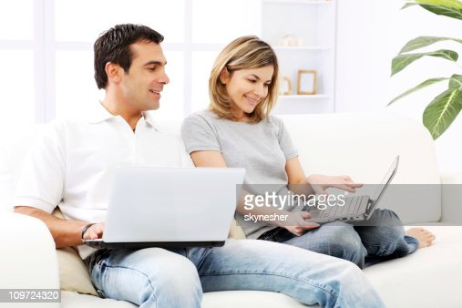 Happy couple sitting together on a sofa , using laptops.