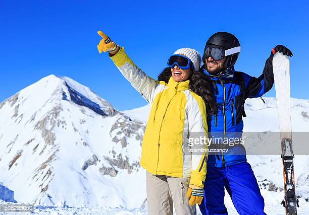 Happy couple skiers resting on top of the snow mountain