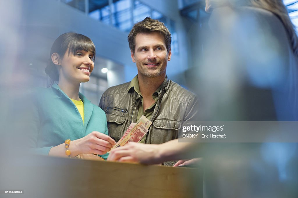 Happy couple standing at a bank counter
