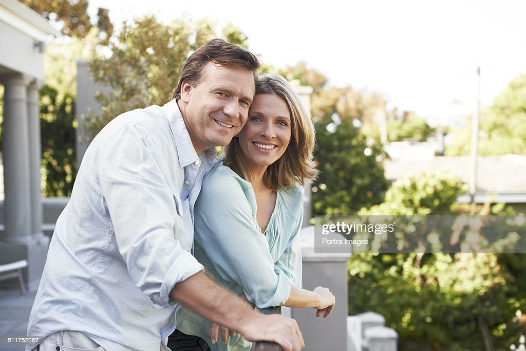 Happy couple standing on balcony