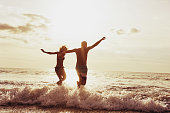 Happy couple having fun and jumps to sunset sea. Beach travel concept