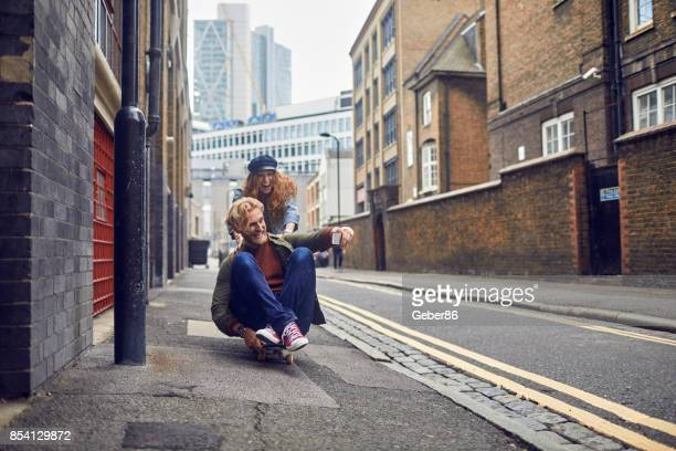 Happy couple taking a selfie while skateboarding