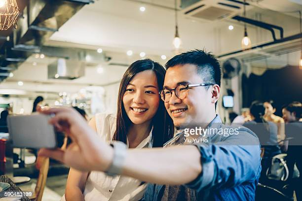 Happy couple taking selfie with smartphone in cafe