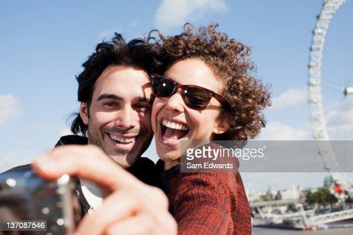 Happy couple taking self-portrait with digital camera near ferris wheel : Stock Photo
