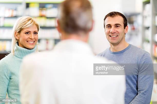 Heureux couple parler à un Pharmacien dans la pharmacie.
