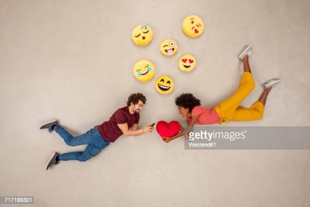 Happy couple texting on their smart phones, sending emojies