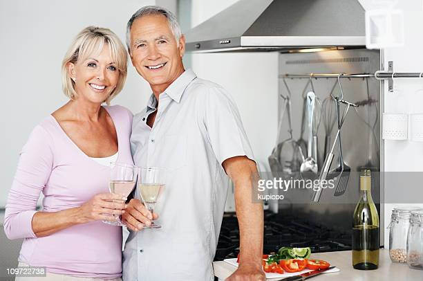 Happy couple together holding champagne glasses at kitchen