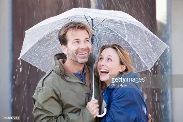 Happy couple under umbrella in downpour