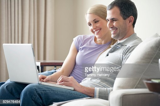 Happy couple using a laptop : Stock Photo