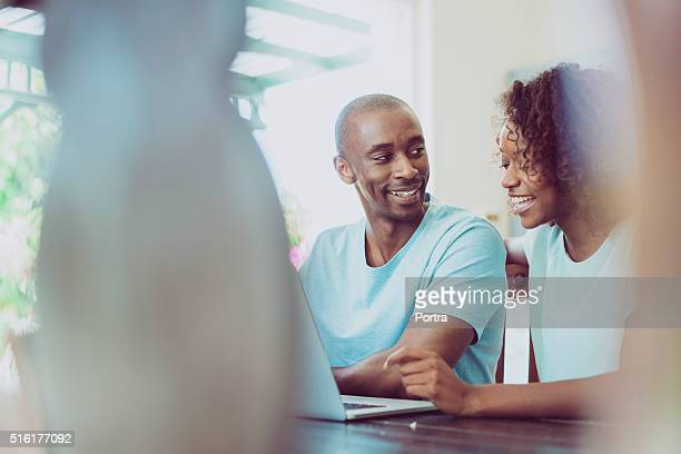 couple heureux à l'aide d'ordinateur portable à la maison